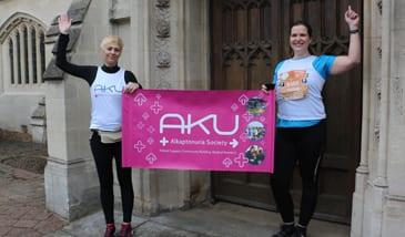 two aku runners holing an AKU society  banner